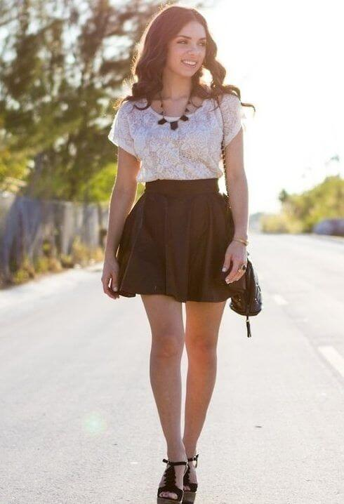 Model sizzles in a black flared mini skirt, white lace top, black heels and a statement necklace to match