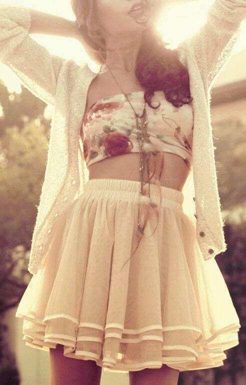 White mini skirt, a floral crop top and white sweater with statement necklace to accessorize