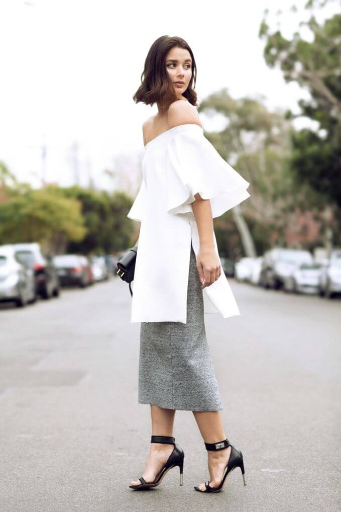 Model sports a crisp white off-shoulder top and gray skirt, sexy strappy heels to slay