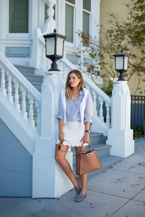Model is in a white scallop skirt, blue shirt with a white sweater hanging from shoulders, nude bag and flats