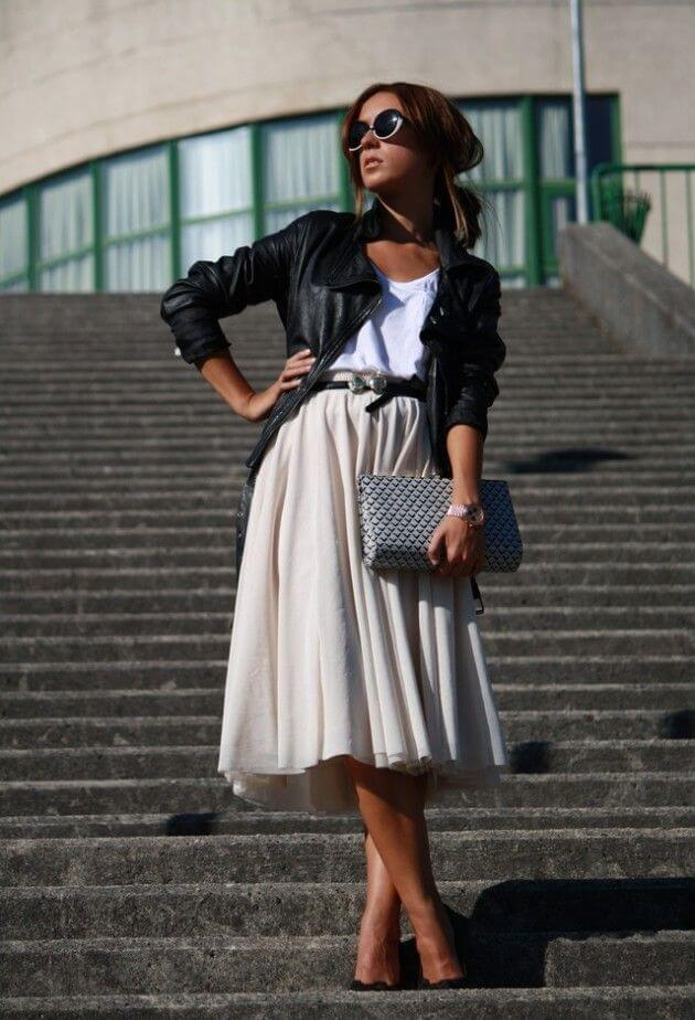 Model poses with a white shirt and leather jacket, beige midi skirt, heels and a clutch bag and bold sunglasses