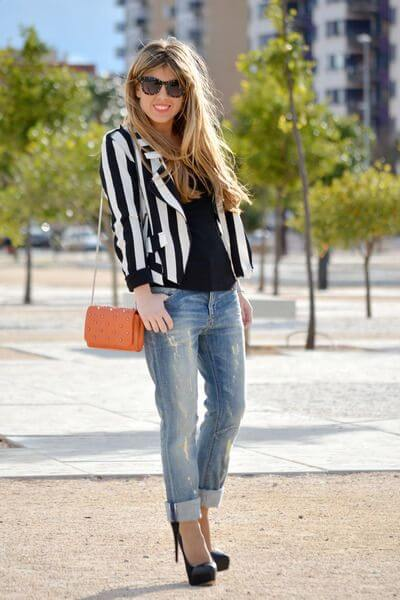 Model looks happy in her plain black top under her white striped jacket, denim jeans and black heels, an orange sling bag and statement glasses for flare