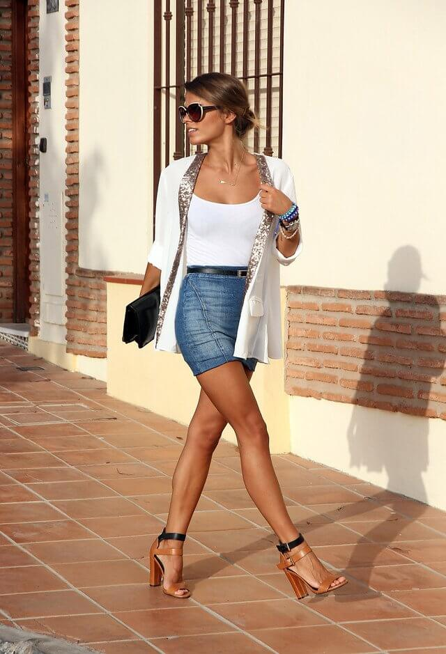 Model walks with a white shirt and matching sparkly blazer, a belted denim skirt, sexy heels and a black clutch bag with statement sunglasses