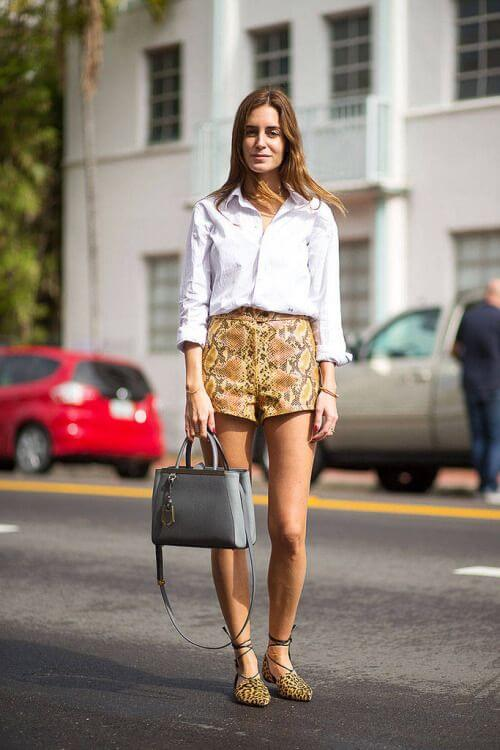 Model in a white collared shirt, animal print high waisted shorts and flats with a bag to accessorize