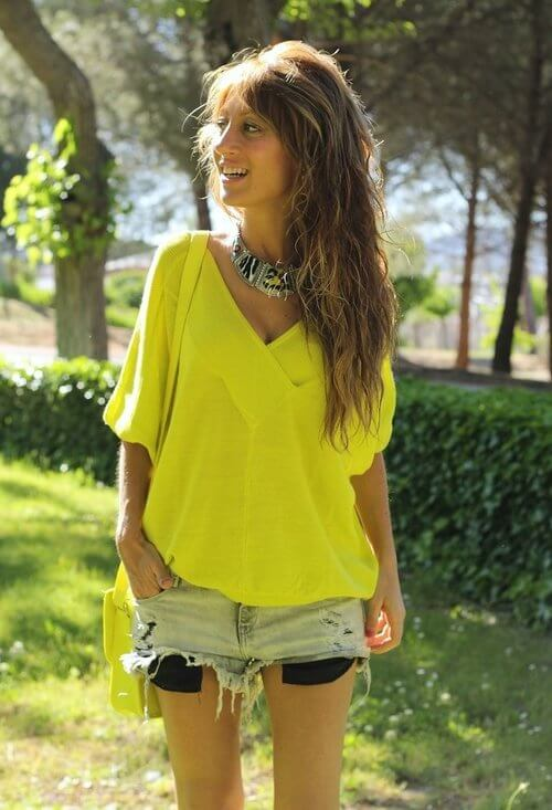 Model walks around in an oversized bright yellow shirt, denim skirt, a yellow bag and a statement necklace