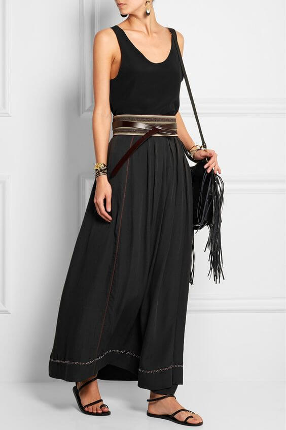 Woman in long silk skirt and simple black vest, together with a strappy leather belt. Black silk skirt and black vests create a nice casual look.