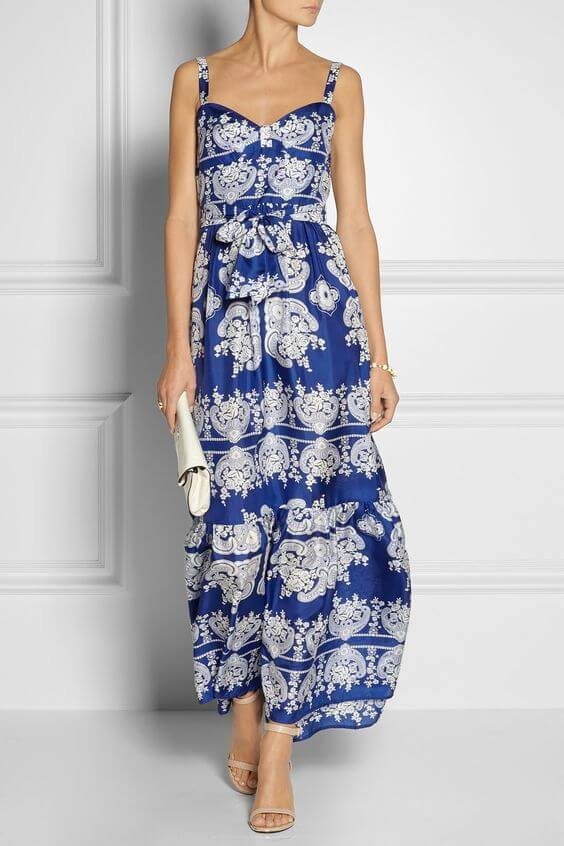 Woman in patterned blue and white dress with white accessories. Real blue elegance: maxi dress & white accessories.