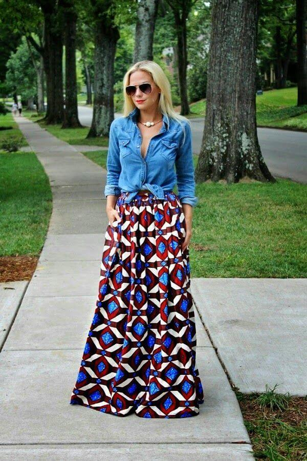woman in the park dressed up in denim shirt and long geometrically patterned skirt