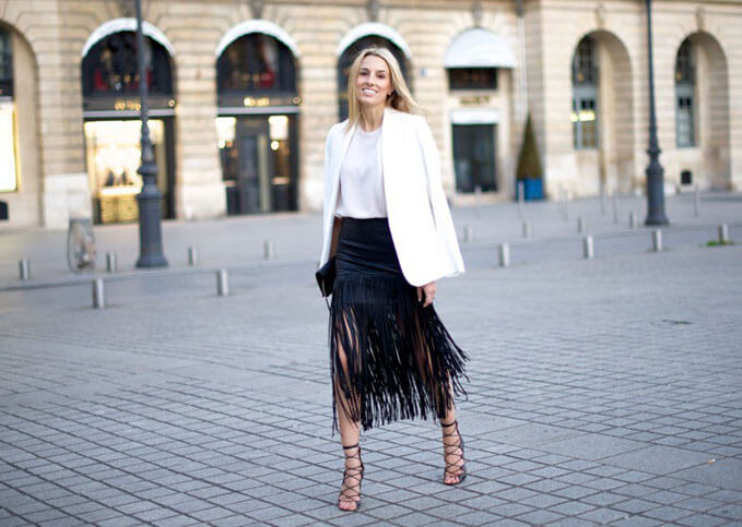 Woman on the street in black fringed skirt with white jacket and blouse