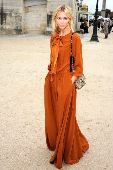 Woman in the street wearing a draped orange maxi dress. Light and long maxi dress in orange.