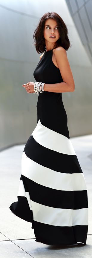 An elegantly looking woman with a maxi A-line skirt and pearl bracelets