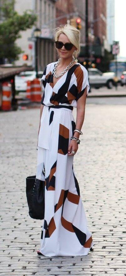 Woman on the street with long white dress with black and brown patterns. White maxi dress with black and brown patterns.