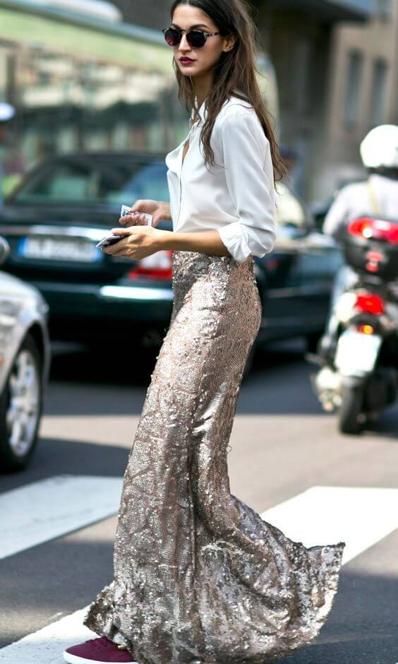 street styler woman wears white button-down blouse and metallic coated maxi skirt