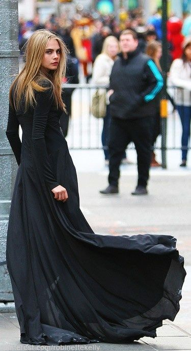 Model in the form-fitting, figure-hugging long-sleeved black maxi dress