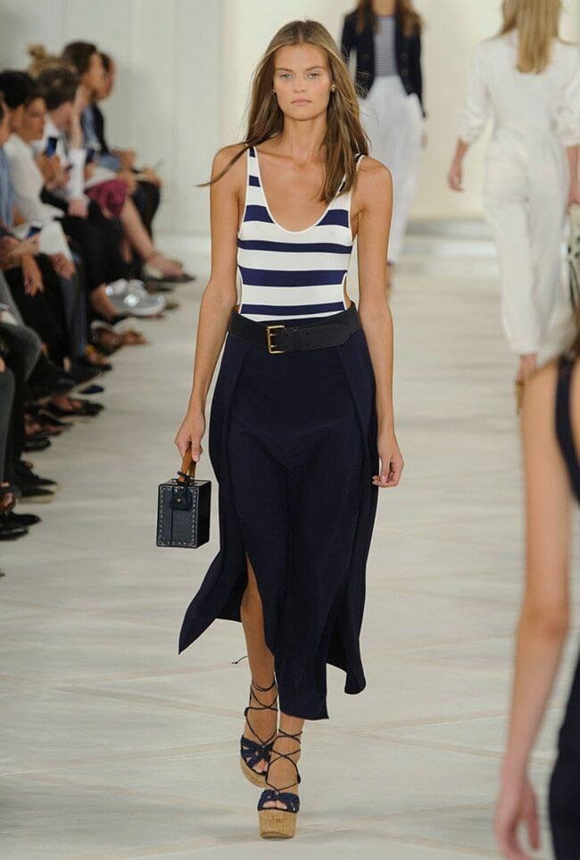 model in nautical theme: layered maxi skirt in navy blue with a striped navy and white vest. Nautical colored maxi skirt and striped vest.