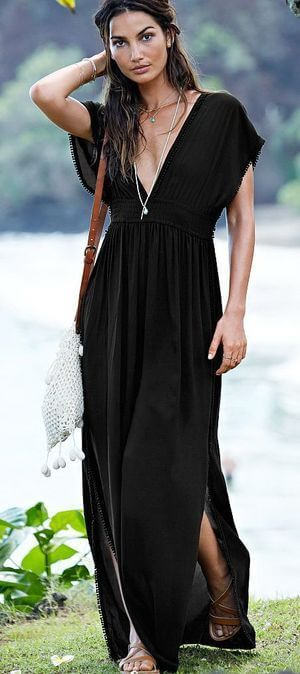Woman standing outside in black cover-up maxi dress. Maxi dress suitable for relaxing summer vacations.