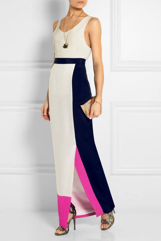 Woman in a slim maxi dress, decorated with elements of white, navy, blue and magenta. Simplicity is a key to elegance.