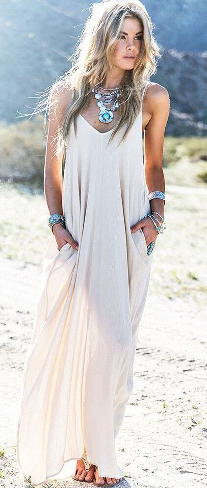 Woman outdoors in light long white dress. Easy and elegant white maxi dress.