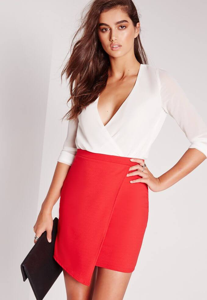 Model dons a vibrant red skirt cut asymmetrically paired with a soft white crossover blouse and a black clutch bag