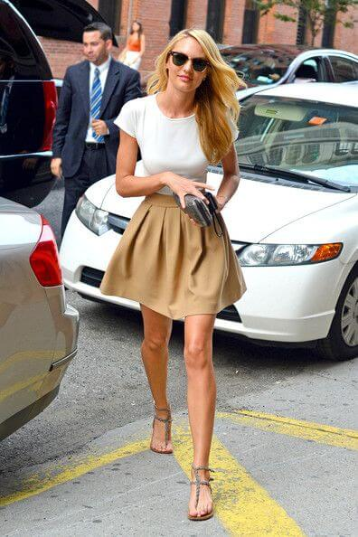 Model looks casual in a beige skirt and simple white shirt, flat thong sandals and black sunglasses to complete the look