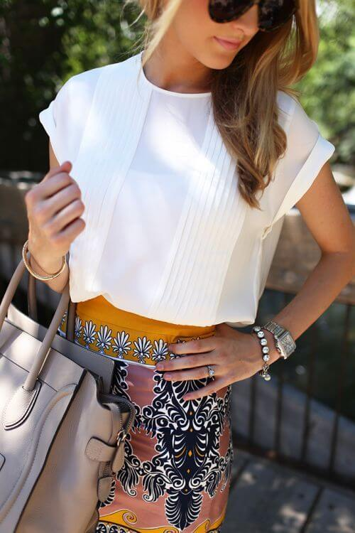 Model is wearing a white pleated chiffon top and cuffed sleeves with a patterned skirt