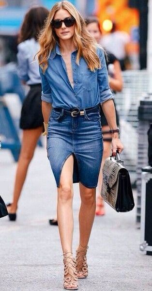 Model struts in a denim button-down blouse casually rolled up at the sleeves, slim-fitting denim skirt with a front skirt and nude strappy sandals to complete