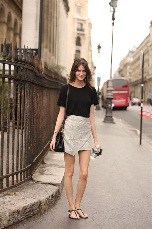 Model keeps it cool by pairing a beige linen wrap skirt with a loose black shirt tucked in, studded thong sandals to complete the look