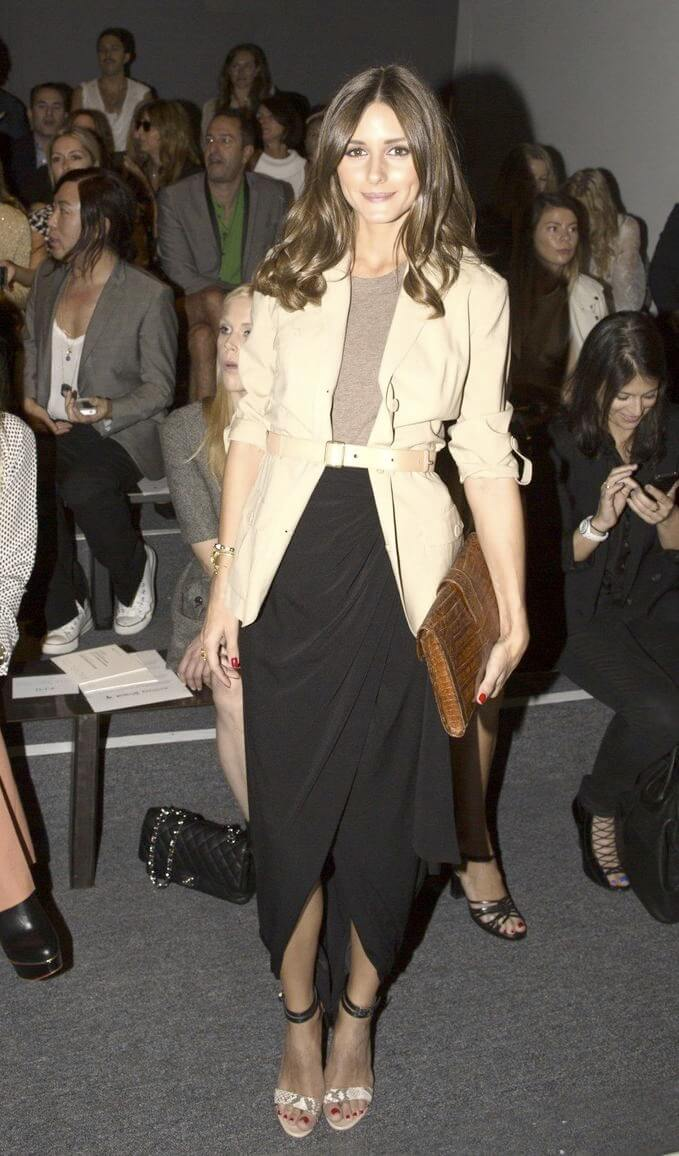 Model poses in a black tulip hem wrap skirt, brown vest and beige trench belted at the waist, a hint of animal print on open toed-stilettos