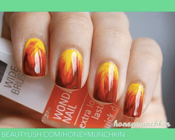 Yellow base nails with wavy orange streaks to red and dark red
