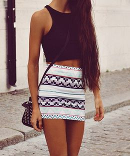 Model wears a mini skirt in funky designs paired with a simple black midriff, a sling bag to accessorize