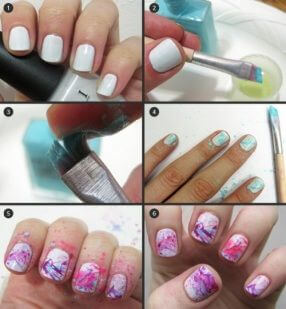 Nails are painted with a white base color and splattered with other colors