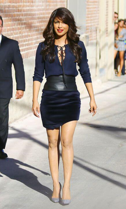 Model flatters in a navy blue lace-up top, velvet mini skirt and a thick leather belt to add dimension