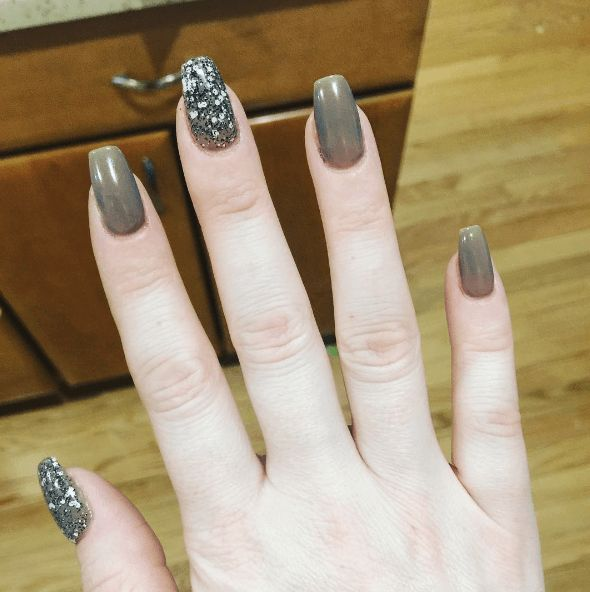 Taupe nails with glitter on thumb and middle finger