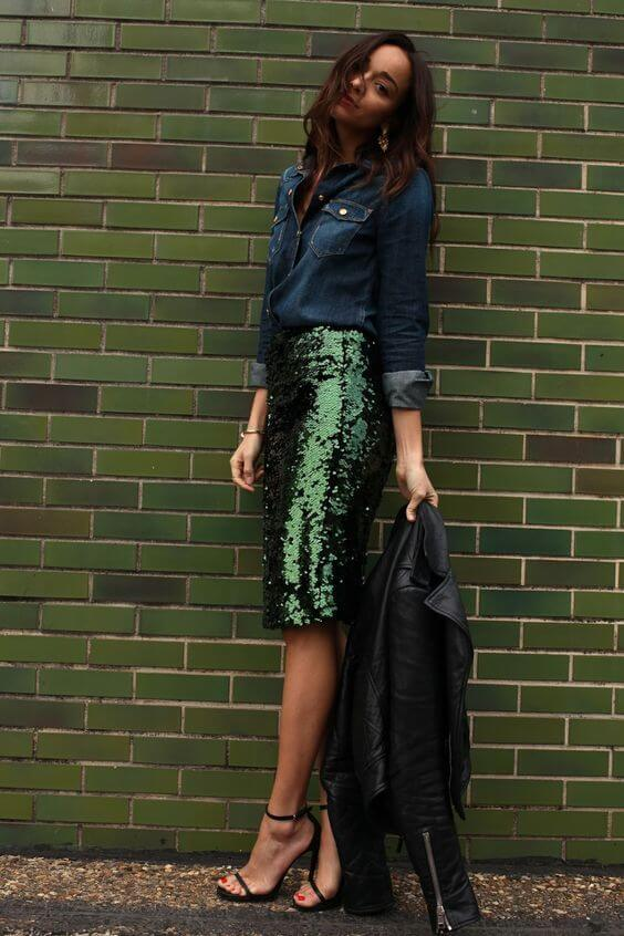 Model looks sexy in a sparkly pencil skirt in sequins with a denim top and strappy black sandals