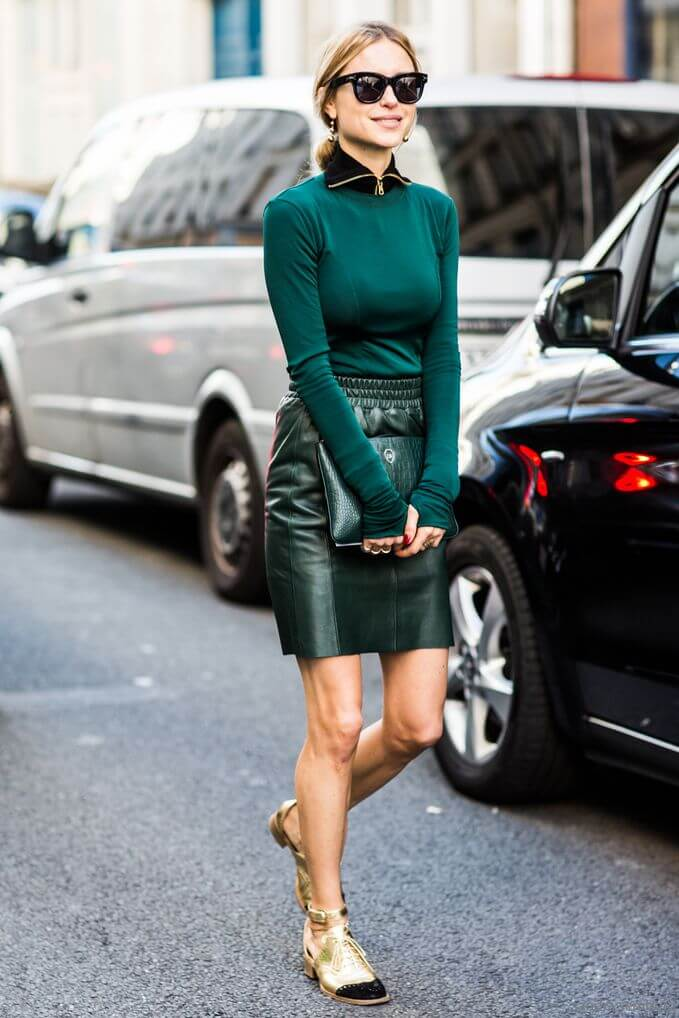 Model stuns in a leather skirt with sporty rouching on the waist and a quirky long-sleeved top with a zip neckline, a green Leowulff clutch purse is a winner