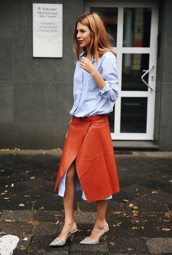 Model gets creative in a rust-colored leather wrap skirt layered over a longer length button-down blouse in pale blue, striped pointy sling-back heels complete the look