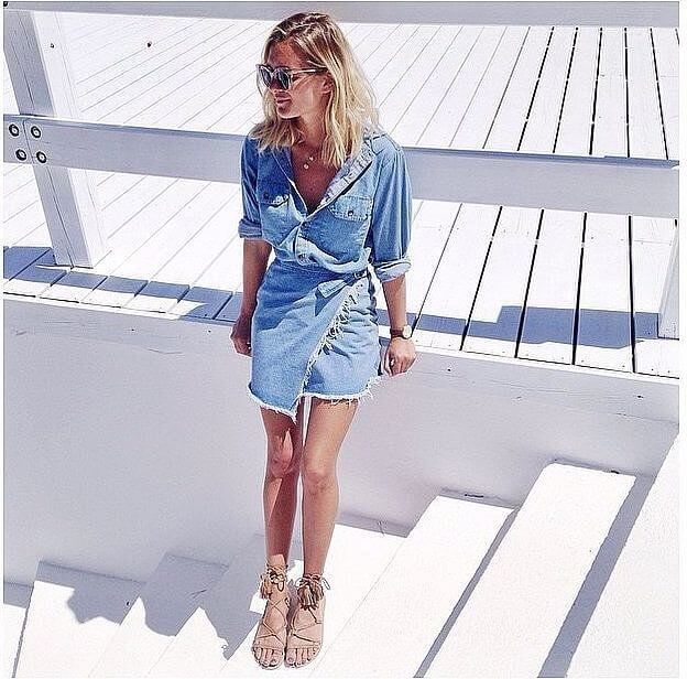 Model is wearing a denim wrap skirt casually paired with a button-down blouse with rolled up sleeves in denim, flat lace-up sandals keep a relaxed vibe