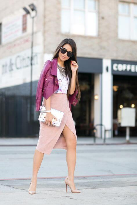 Model is in a pale pink suede midi wrap skirt paired with a graphic tee and jacket in bright magenta, nude stilettos make the legs appear longer