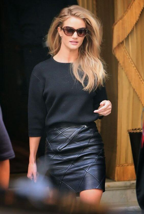 Model wears a black leather skirt and a loose black top, statement glasses to pull off