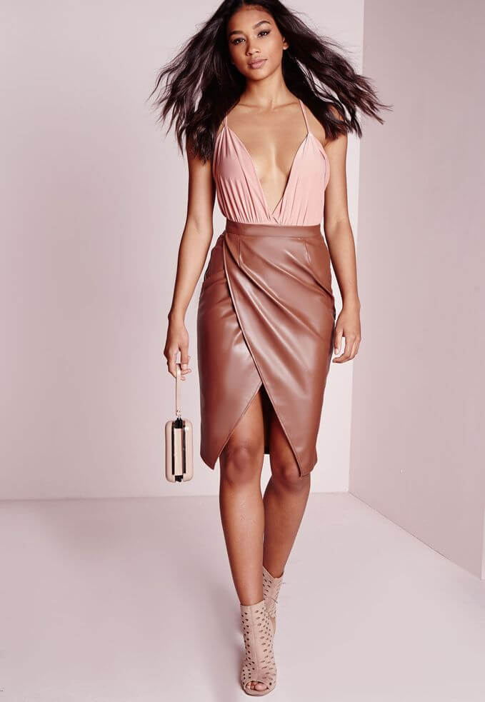 Model features a high waistline, tan wrap skirt in draped faux leather to a soft pink camisole top, nude suede heels and a clutch purse to complete