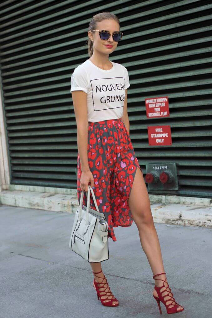 Model catwalks in a red and gray patterned skirt and white patterned top, a handbag and red strappy sandals