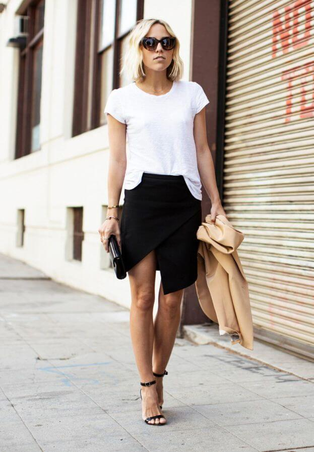 Model looks classy in an asymmetrical black wrap skirt, plain white shirt tucked fashionably in the front, black stilettos tied at the ankle elongate her legs