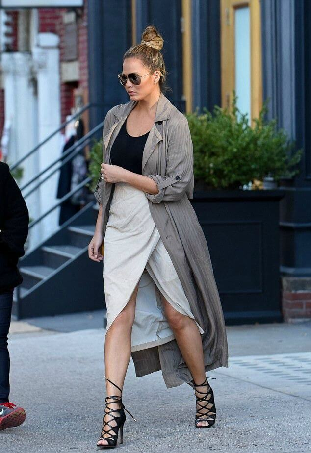 Model dons a softly draped beige wrap skirt with plain black vest and a darker trench coat, the stilettos give the look edginess