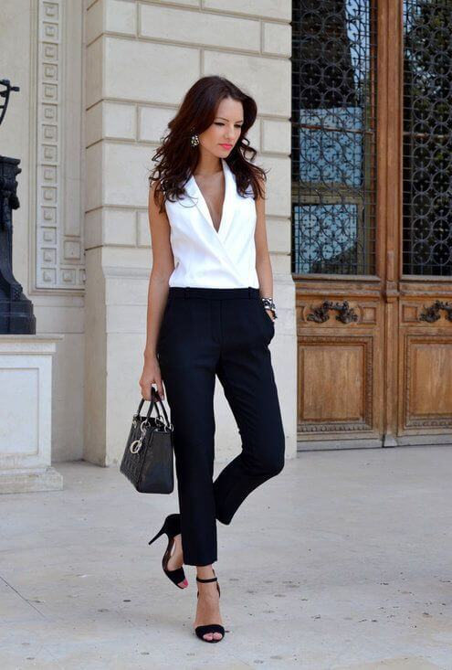 Model walks about in a white sleeveless blouse, ankle-skimming navy blue pants, strappy open-toed sandals and a black handbag to polish off this office look