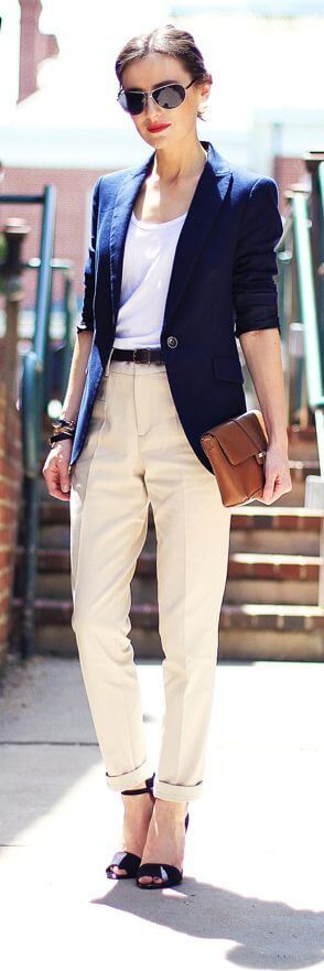 Model wears a simple white vest with beige slouchy pants and a dark navy blue blazer, the skinny brown belt adds a fun touch to this look