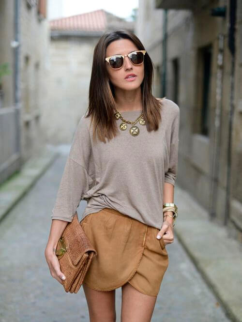 Model looks carefree in a soft suede wrap skirt and loose-fitting gray-brown top, accessories are in earthy tones to match