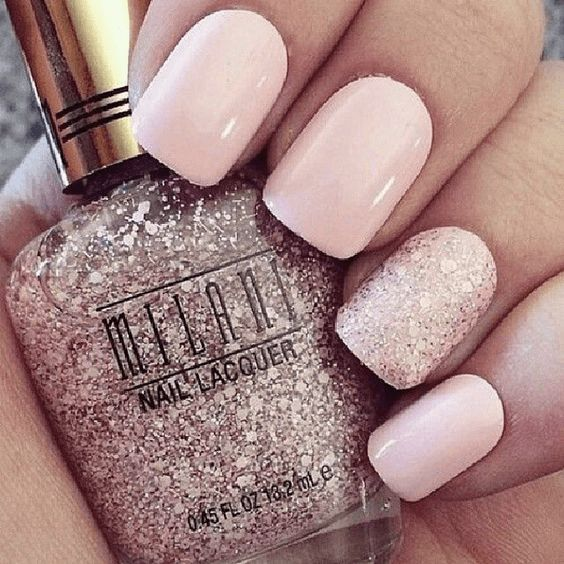 Nude nails are paired with glitter polish on ring finger