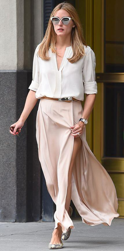 Model wows in a soft white button-down blouse paired with pale pink maxi skirt with thigh-high split. polishing the look with trendy sunglasses, a tan belt and flat ballet pumps