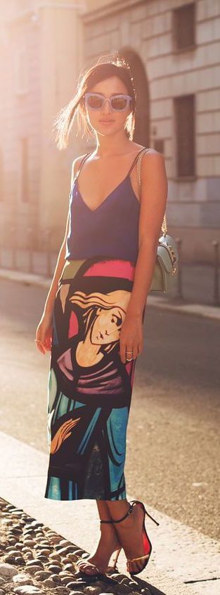 Model poses in a bold, bright skirt paired with light silk camisole and slinky heels