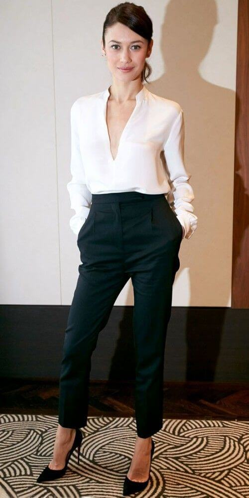 Model poses in high-waisted black fitted pants and silky cream blouse with a deep V neckline, stilettos to add edge
